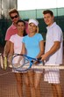 Young friends on tennis court smiling