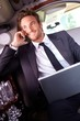 Happy businessman on phone call in limousine