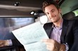Happy man reading news in luxury car