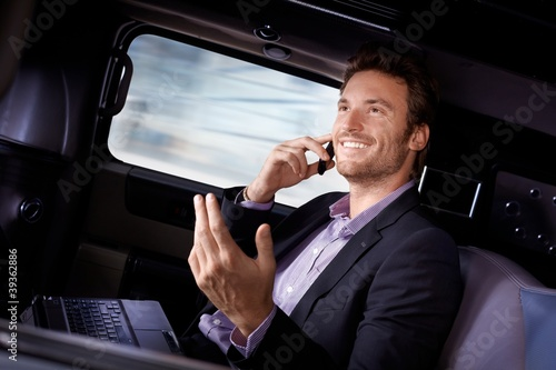 Handsome businessman traveling in limousine