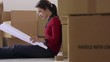 woman reading plans of new house during move