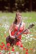 Mädchen mit Gitarre im Blumenfeld