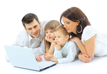Loving family looking at a laptop lying down on bed