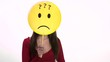 Confused young woman using emoticon for emotions