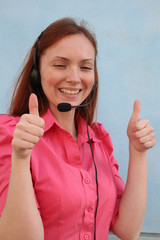 Woman with headset gesturing thumbs up