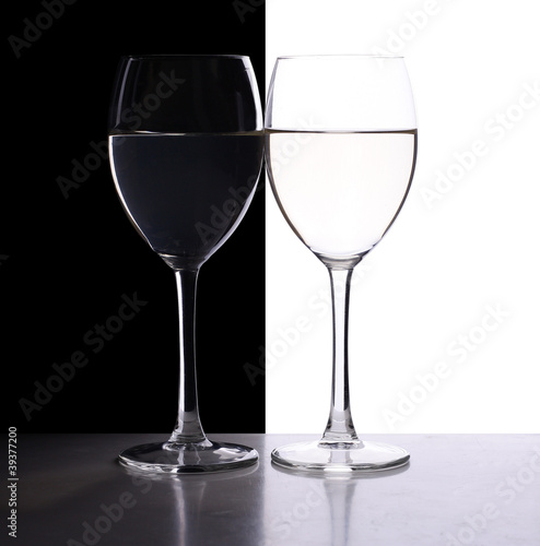 two wine glasses in backlight on the black and white background