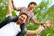 Father giving his son piggyback ride outdoors in park