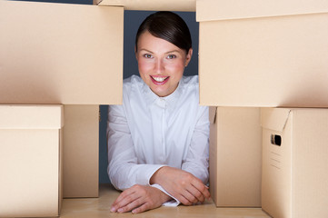 Portrait of young woman surrounded by lots of boxes
