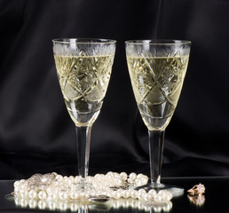 White vine glasses with white beads and wedding ring