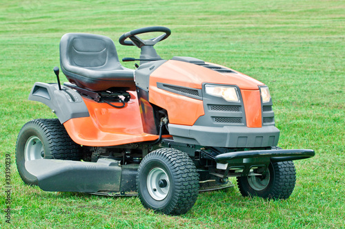 Petrol lawn mower with the lights on on green grass background