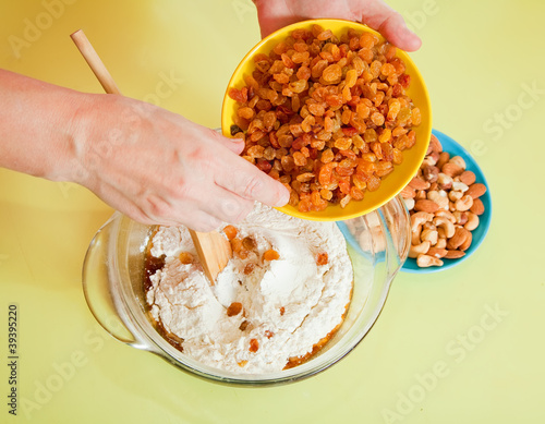 Closeup of woman adds raisin into dough