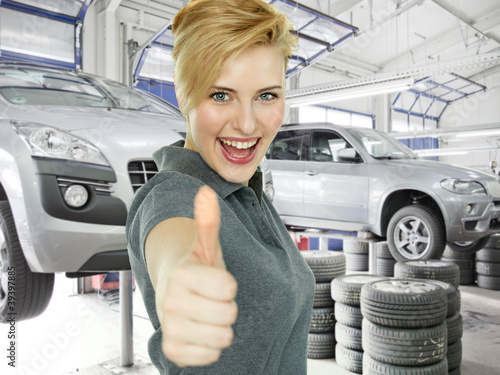 Young woman shows thump up in a garage after tyre changing