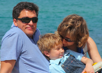 portrait of a happy family on the background of the sea