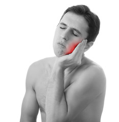 young man holding his aching tooth in pain, isolated on white ba