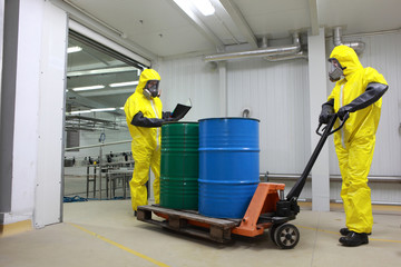 Two specialists in protective uniforms dealing with barrels