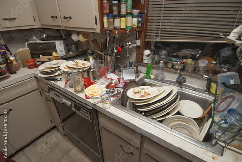 Dirty dishes piled up in sink after a party - 39405233