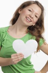 Dynamische junge Frau mit weißem Herz in der Hand