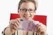 Junge Frau zeigt voller Freude fünfhundert Euroschein