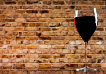 glass of wine on the background of a brick wall