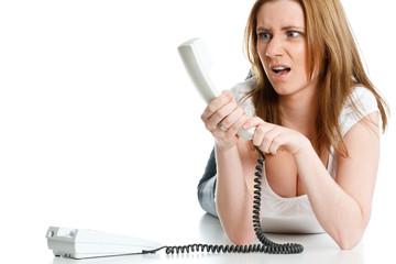 junge frau schaut verständnislos den telefonhörer an