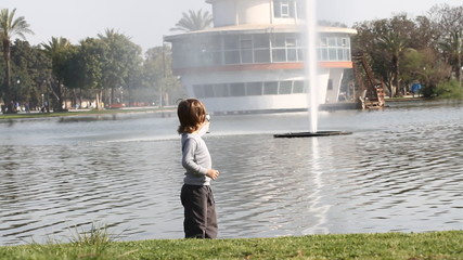 Boy tries to get water from the fountain on the lake