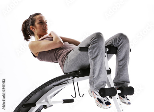 Woman using fitness machinery, white background