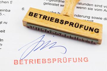 Holzstempel auf Dokument: Betriebsprüfung