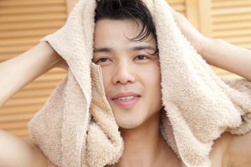 タオルで頭を拭く男性