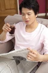 アイスコーヒーを飲みながら新聞を読む男性