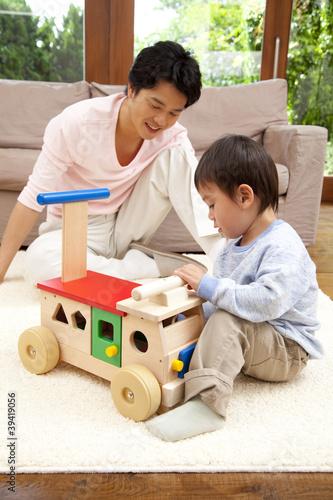 手押し車で遊ぶ父親と息子