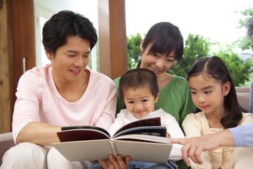 子供達に本を見せる両親