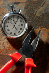 Stopwatch and pliers on the rusty plate