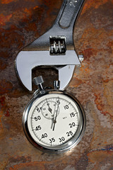 Spanner and stopwatch on the rusty plate