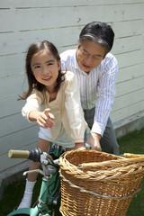 自転車に乗る練習をする孫娘と自転車を支える祖父