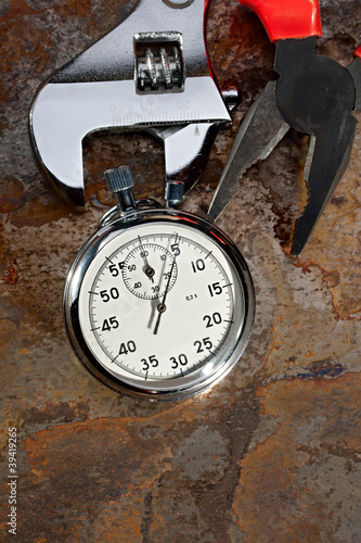 Spanner, pliers and stopwatch on the rusty plate