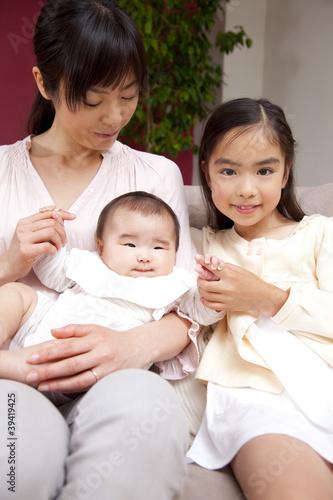 ソファに座る母親と子供達