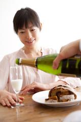 シャンパンをグラスに注いでもらう女性