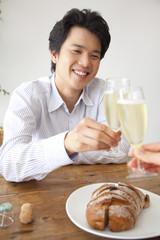シャンパンで女性と乾杯をする男性