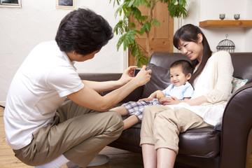 デジカメで家族を撮影する父親