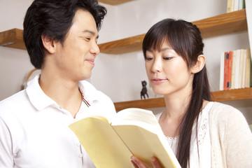本を手にとって見るカップル