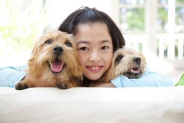 2匹のノーフォークテリアを抱き寄せる笑顔の女の子