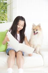 本を見るポメラニアンと女の子