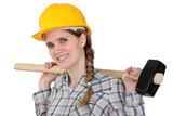 Woman holding sledge-hammer over shoulder