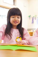 折り紙を折る幼稚園女児