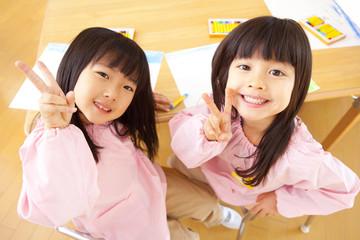 ピースサインをする幼稚園女児2人