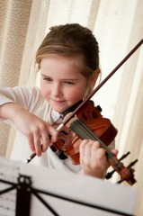 Child playing violin at home