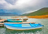 Old wooden fishing boats in the lake Prespa in Greece. poster
