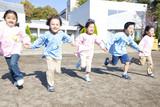 手を繋いで園庭を走る幼稚園児5人