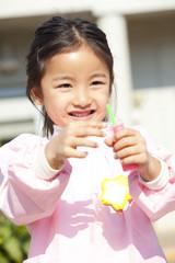 シャボン玉で遊ぶ笑顔の幼稚園女児