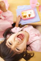 お弁当を食べながらおどける幼稚園女児